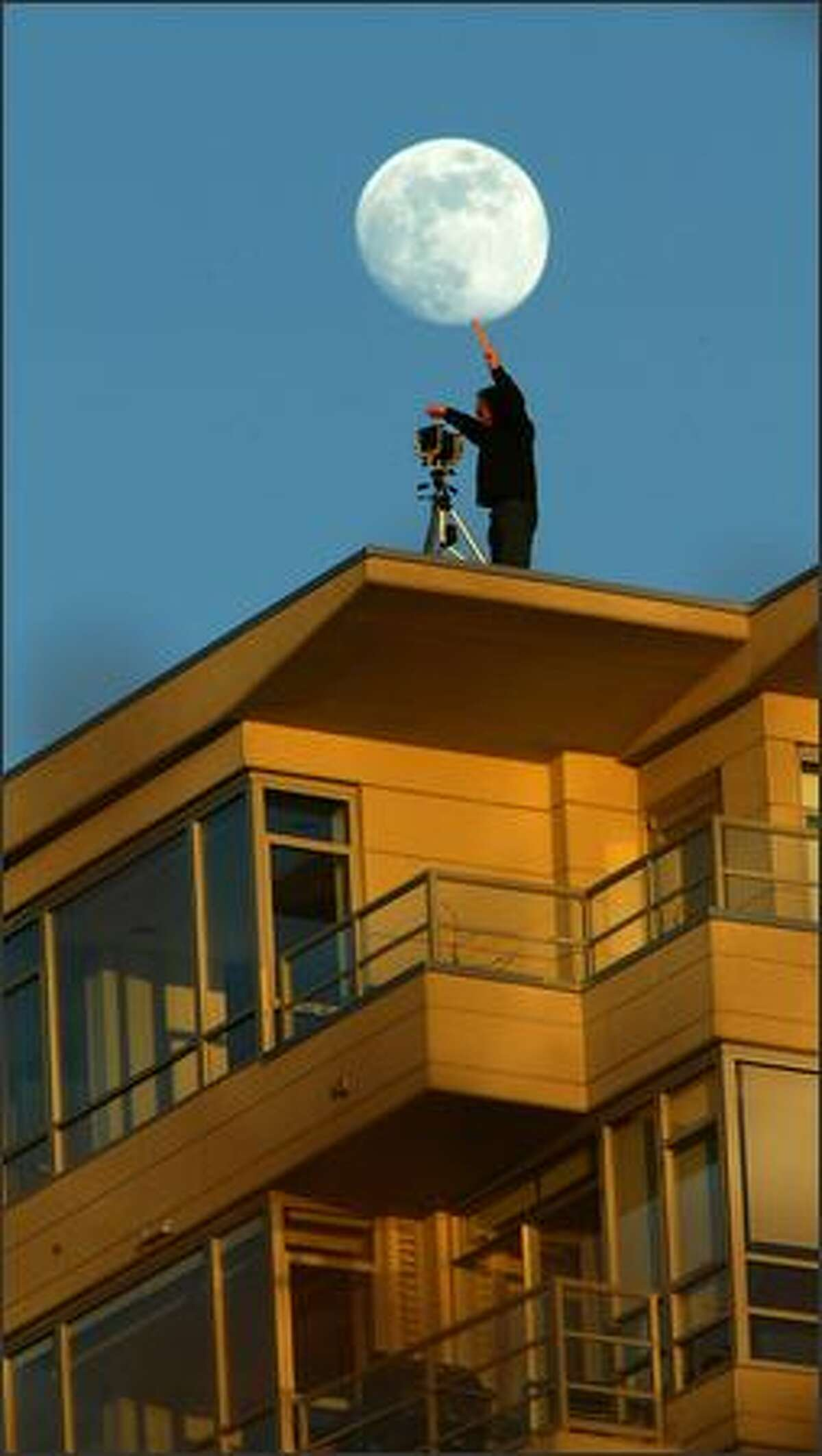 Remember when they told you to shoot with the sun over your shoulder? Well, Dean Wallace turned the old piece of advice around Tuesday at sunset. The moon rises behind Wallace, a commercial photographer, as he uses a film box to shade his lens from the setting sun. Wallace, using a 4x5 camera, is standing on the roof of the 13-story Concord Condominiums to shoot the site of a new building Belltown.