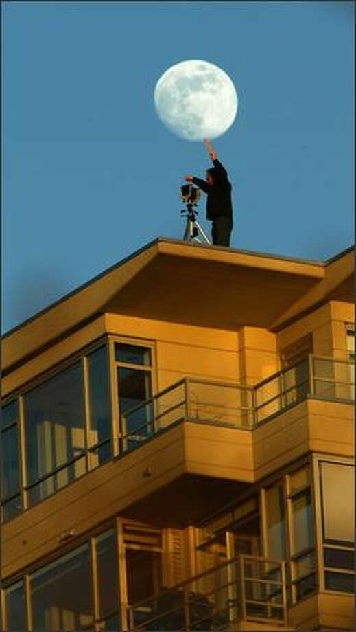 Remember when they told you to shoot with the sun over your shoulder? Well, Dean Wallace turned the old piece of advice around Tuesday at sunset. The moon rises behind Wallace, a commercial photographer, as he uses a film box to shade his lens from the setting sun. Wallace, using a 4x5 camera, is standing on the roof of the 13-story Concord Condominiums to shoot the site of a new building Belltown. Photo: Grant M. Haller, Seattle Post-Intelligencer / Seattle Post-Intelligencer
