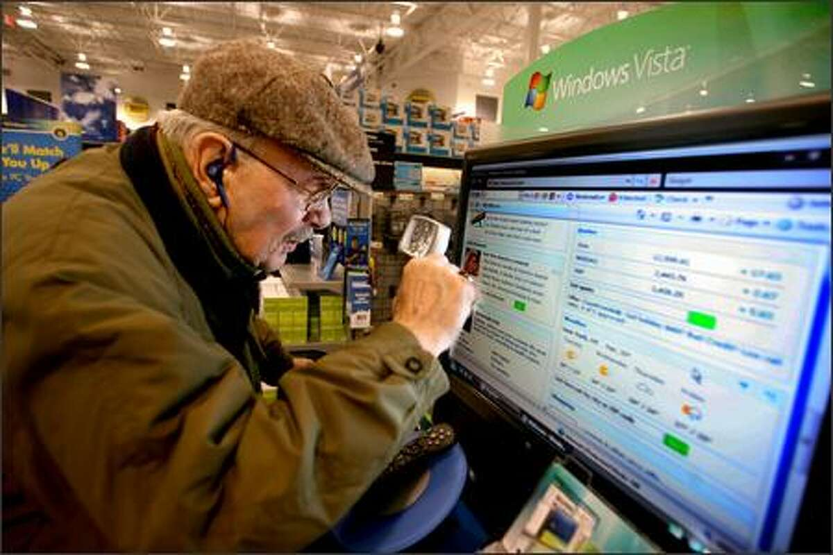 Ted Koch, 83, of Bellevue uses his magnifying glass to get a close-up look at Windows Vista, on display at the Bellevue Best Buy store. Koch suffers from macular degeneration. Vista has a feaure called Magnifier that makes on-screen type larger.