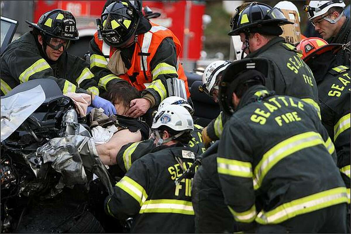 Seattle fire fighters work to extract a 40-year-old woman form a vehicle involved in a head-on collision near the corner of 15th Avenue West and West Armour Street in Seattle.