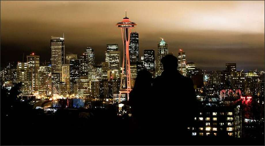 Katie Schnur, left, of Seattle, and Brian Oates, of Lexington, Ky., pause to enjoy the Space Needle and the Seattle skyline from Kerry Park on Queen Anne. The Seattle icon is lit in red to mark National Wear Red Day for Women, which spotlights the problem of heart disease in women. Photo: Grant M. Haller, Seattle Post-Intelligencer / Seattle Post-Intelligencer