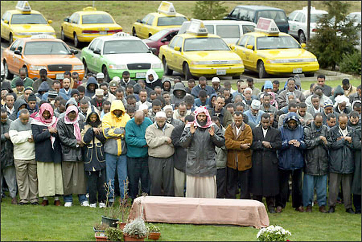 Mourners gather at the Dar-o-Rahma cemetery east of Kent for the funeral of Hassan Farah, a taxi driver slain in South Seattle Saturday morning.