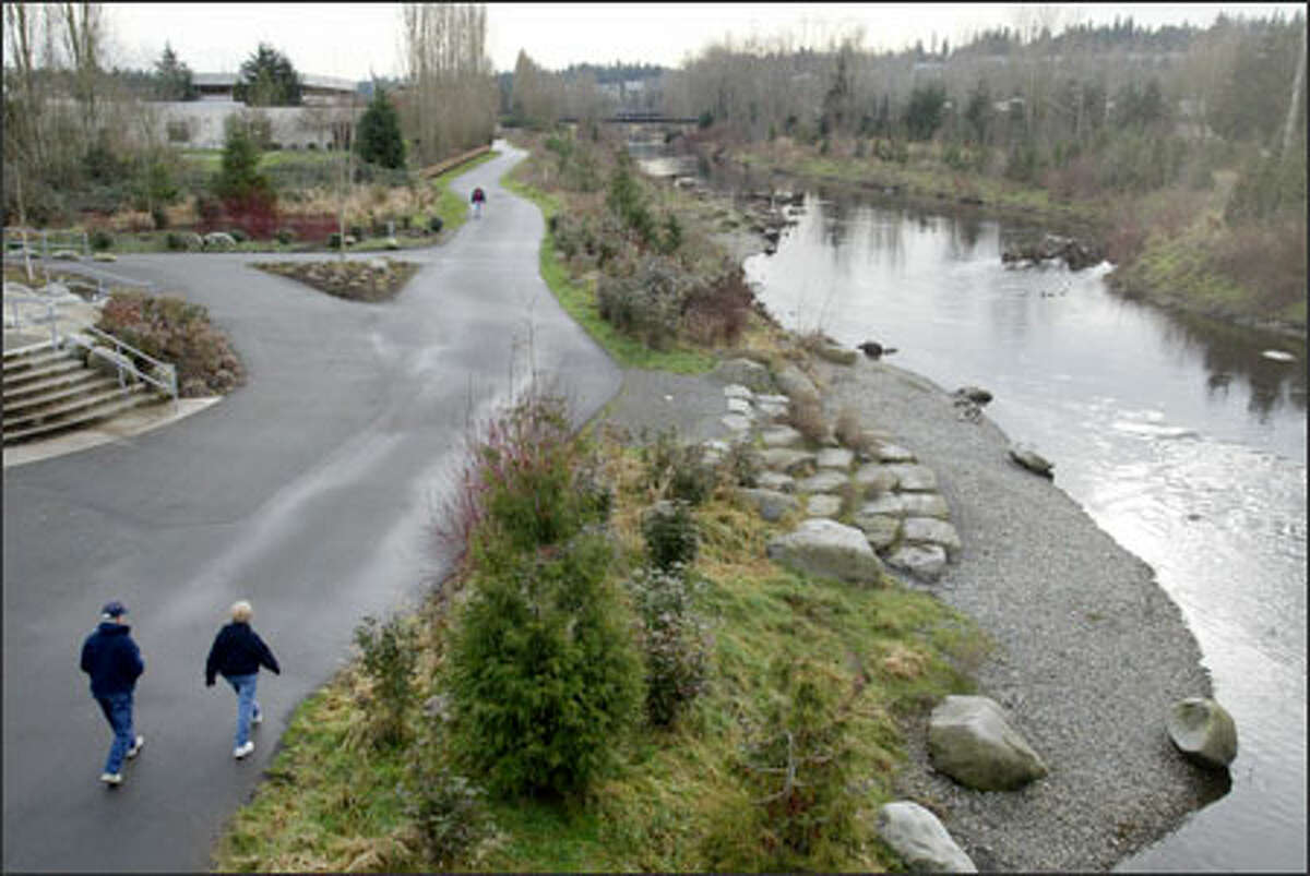 A man and woman stroll the RiverWalk in Redmond, where the Sammamish River is being transformed from