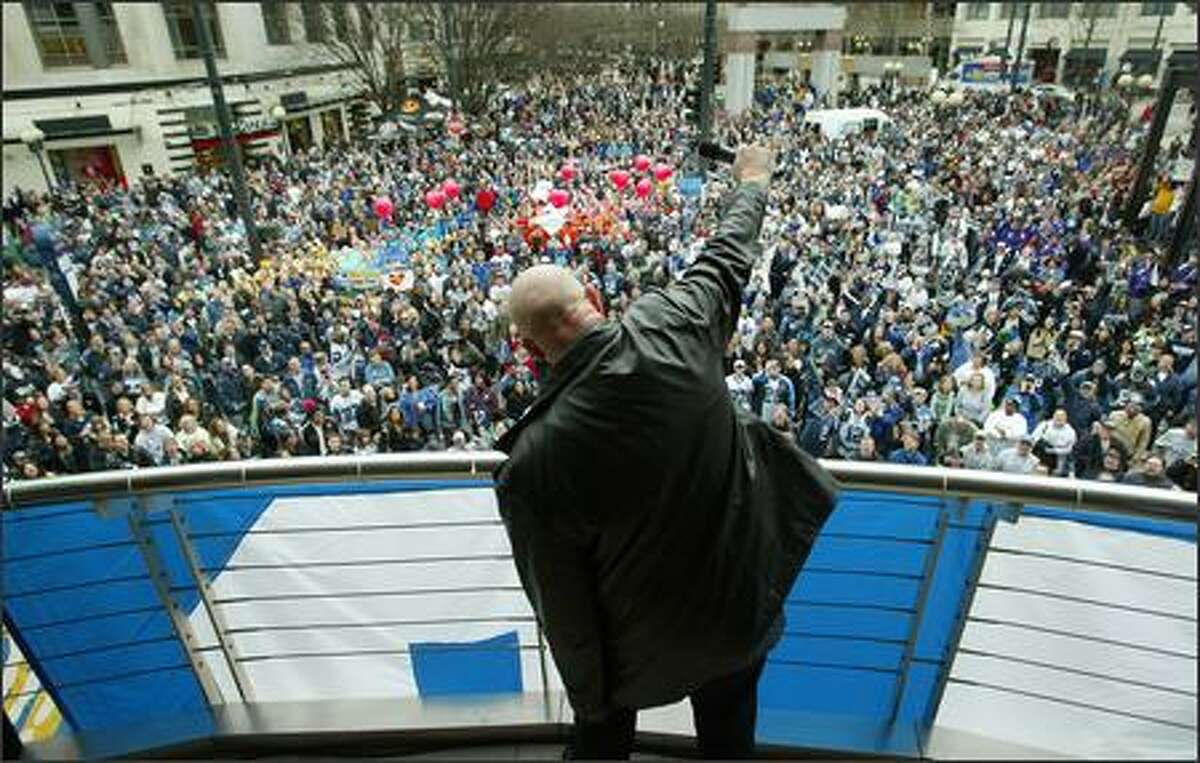 """Singer J.C. Rox leads the crowd in his song """"Seahawk Rock"""" at a Seahawks rally at Westlake Center in Seattle Friday. About a thousand fans who didn't get to go to Detroit for the Super Bowl showed their support for the team."""