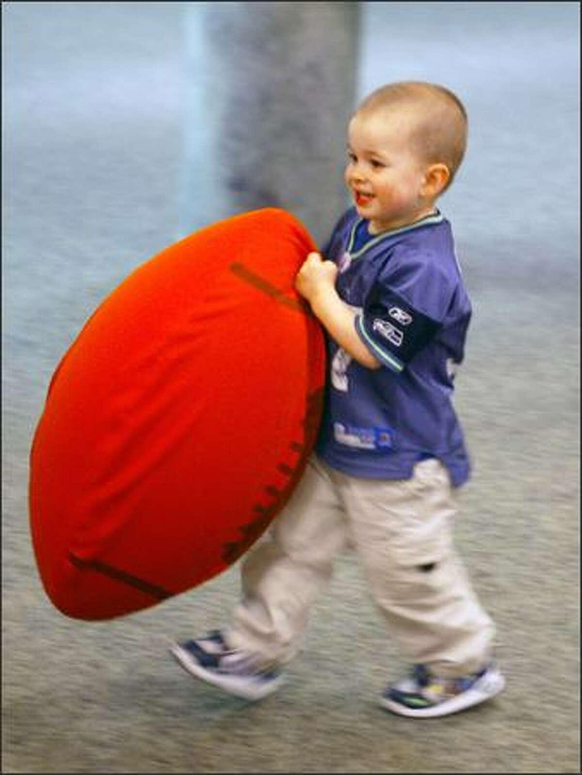 Caleb Nuno, 2, wearing a Shaun Alexander jersey, carries a blow-up football through the Christian Faith Church in SeaTac. The church is attended by Seahawk Shaun Alexander when he is in town.