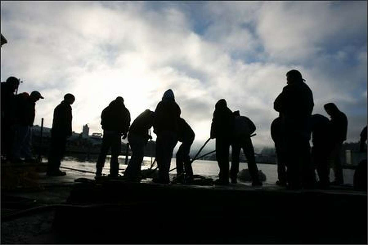 Students from the Divers Institute of Technology are silhouetted against early-morning sunshine as they use long poles to float bags from the dock during a boat-salvaging exercise.