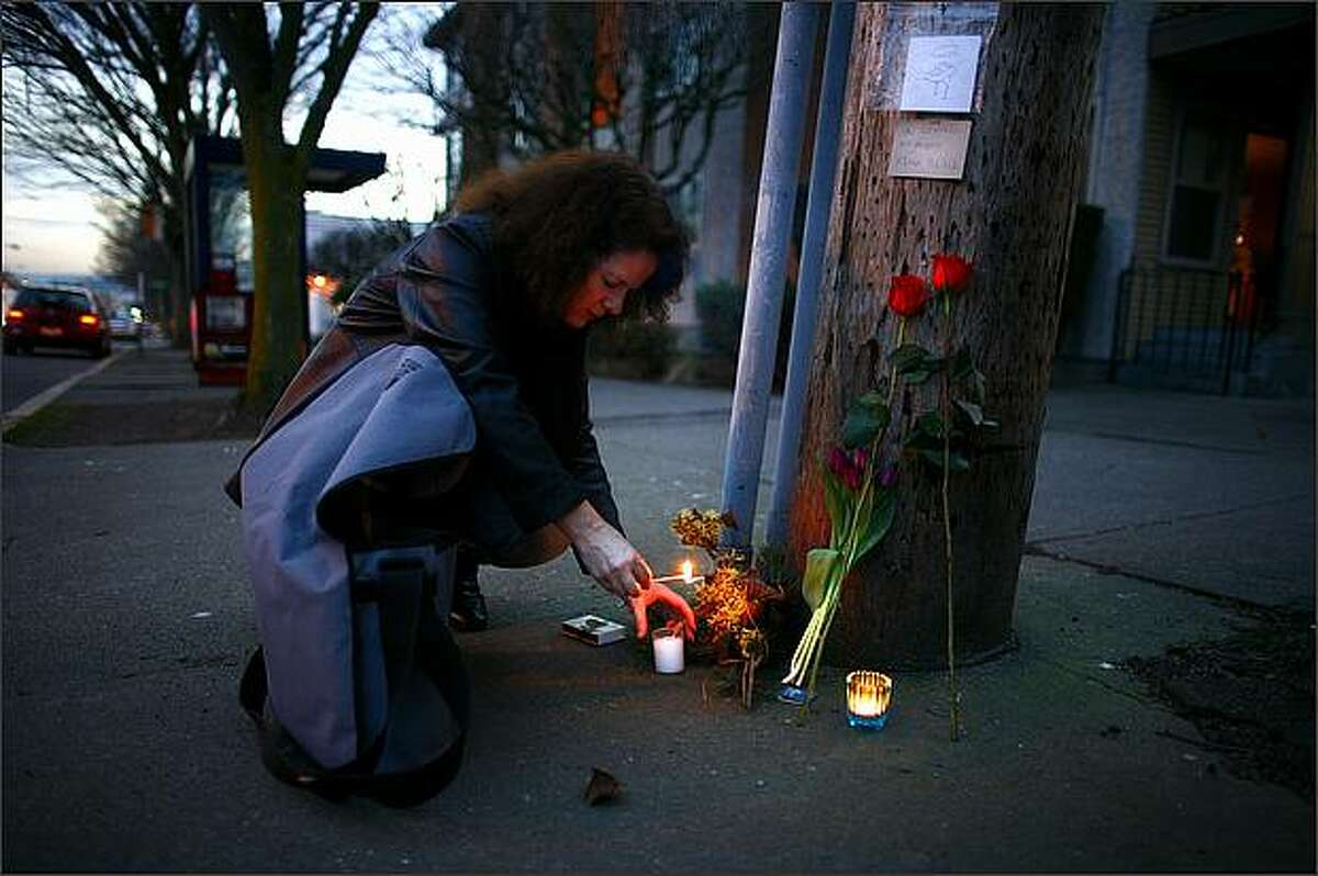 Elizabeth Schirmer lights a candle at a memorial for bicyclist Kevin Black, who died after colliding with a van on 24th Avenue Northwest in Ballard. Schirmer's brother-in-law was involved in a serious motorcycle accident in 2007 at the same intersection. She said the way 24th Avenue Northwest curves at the intersection likely makes it more dangerous.