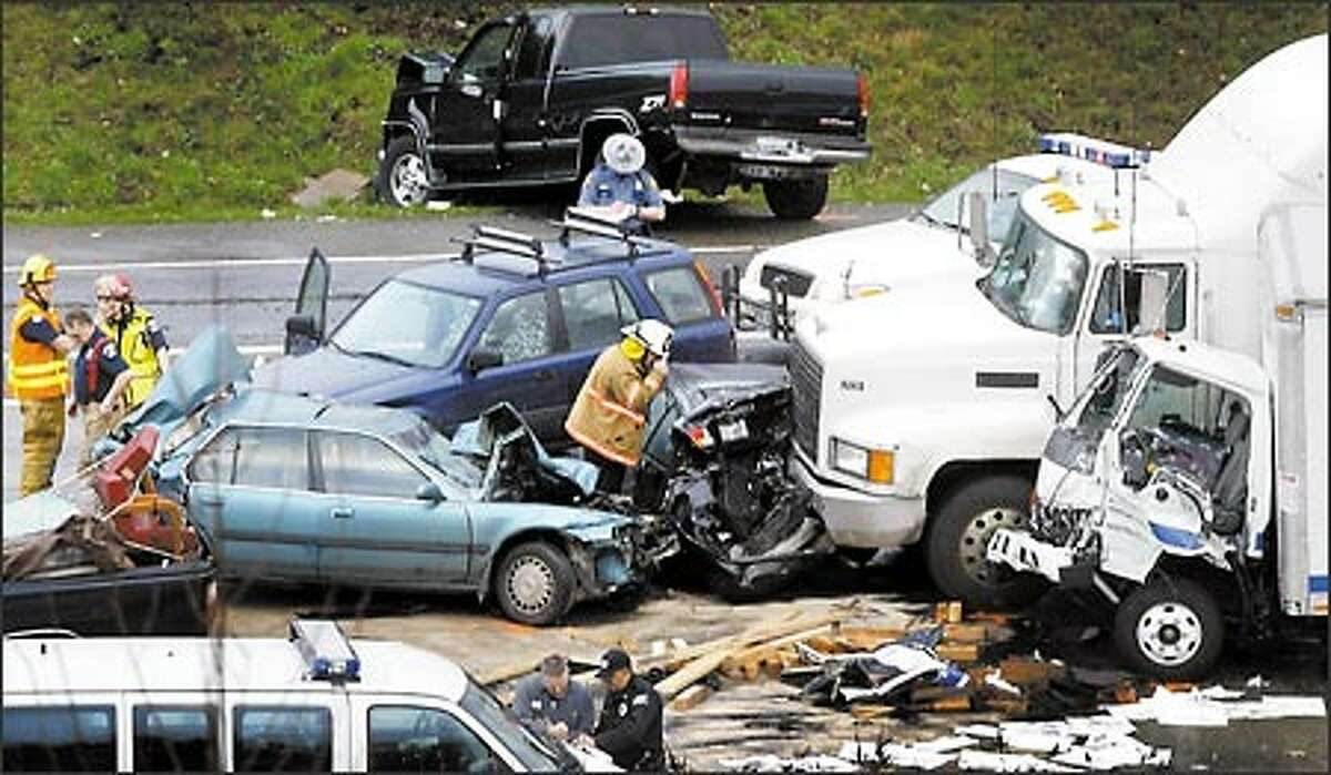 Police officers and rescue personnel investigate a pileup on Interstate 5 near South 188th Street and Orillia Road South Friday. That accident and a number of other collisions, which shut down a stretch of I-5 during afternoon rush hour, as well as a lightning strike at Sea-Tac Airport were blamed on a freak weather system.
