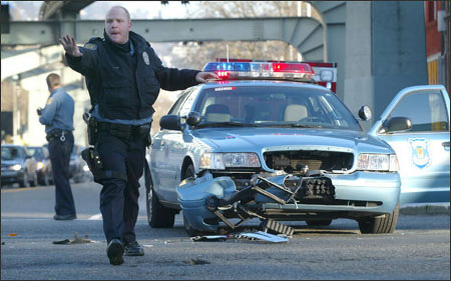 Police direct traffic around the site of an accident involving a police cruiser and another car in downtown Seattle. The police officer -- who was not responding to a call -- was sent to the hospital with minor injuries, and the accident was under investigation. Photo: Joshua Trujillo, Seattlepi.com / Seattle Post-Intelligencer