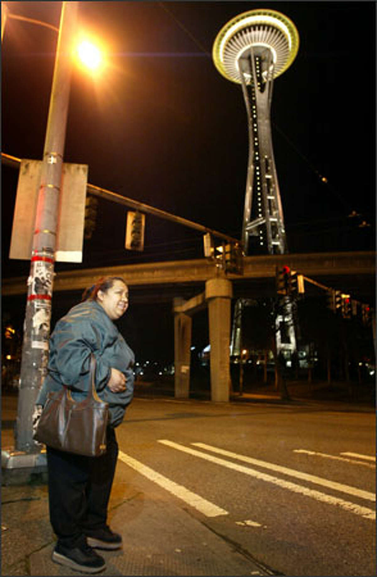 Narciza Pineda, 42, prepares to cross Broad Street on her way to her job as a janitor at the Space Needle, where she earns $10.75 an hour -- more than minimum wage, but barely enough for her family to live on.