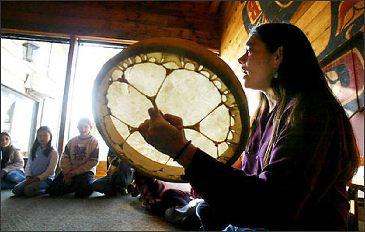 """Chenoa Egawa, a Lummi and S'Klallam Indian singer and storyteller, sings a song to fifth-graders from Highlands Elementary at Ivar's Salmon House. The program was part of """"Salmon in the Classroom,"""" in which students are taught the cultural link between salmon and Native Americans of the Northwest. Ivar's hosted the state Department of Fish and Wildlife program for the students. They had to write Indian legends to qualify. """"With the legend writing, we were able to incorporate language-arts curriculum into this science program,"""" teacher Erica Anderson said."""