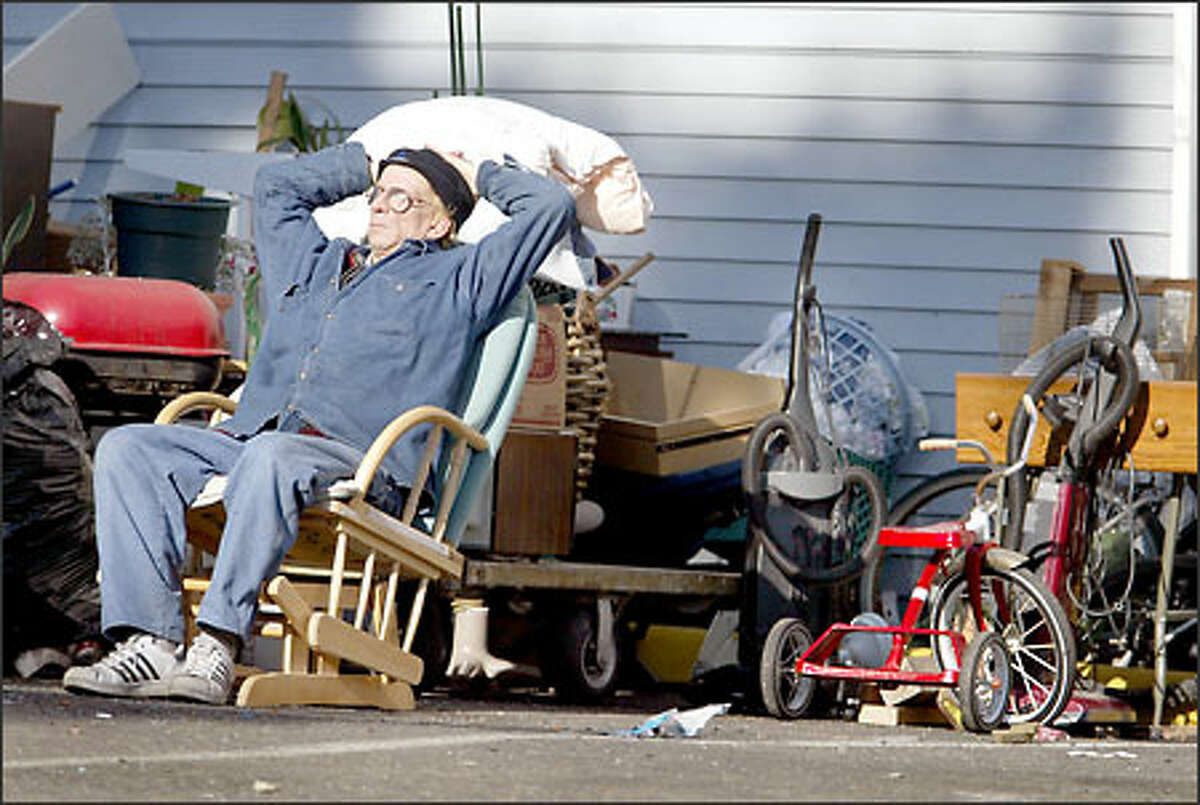 After eviction from the Juanita Apartments in Burien, Jeff Hoskinson waits with his belongings outside the apartment building.