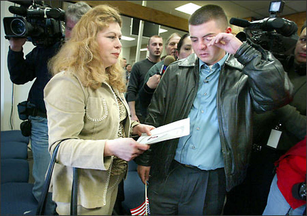 Juan Escalante, with his mother, Silvia, is overcome with emotion while taking his oath to become a U.S. citizen in a ceremony Wednesday in Seattle.