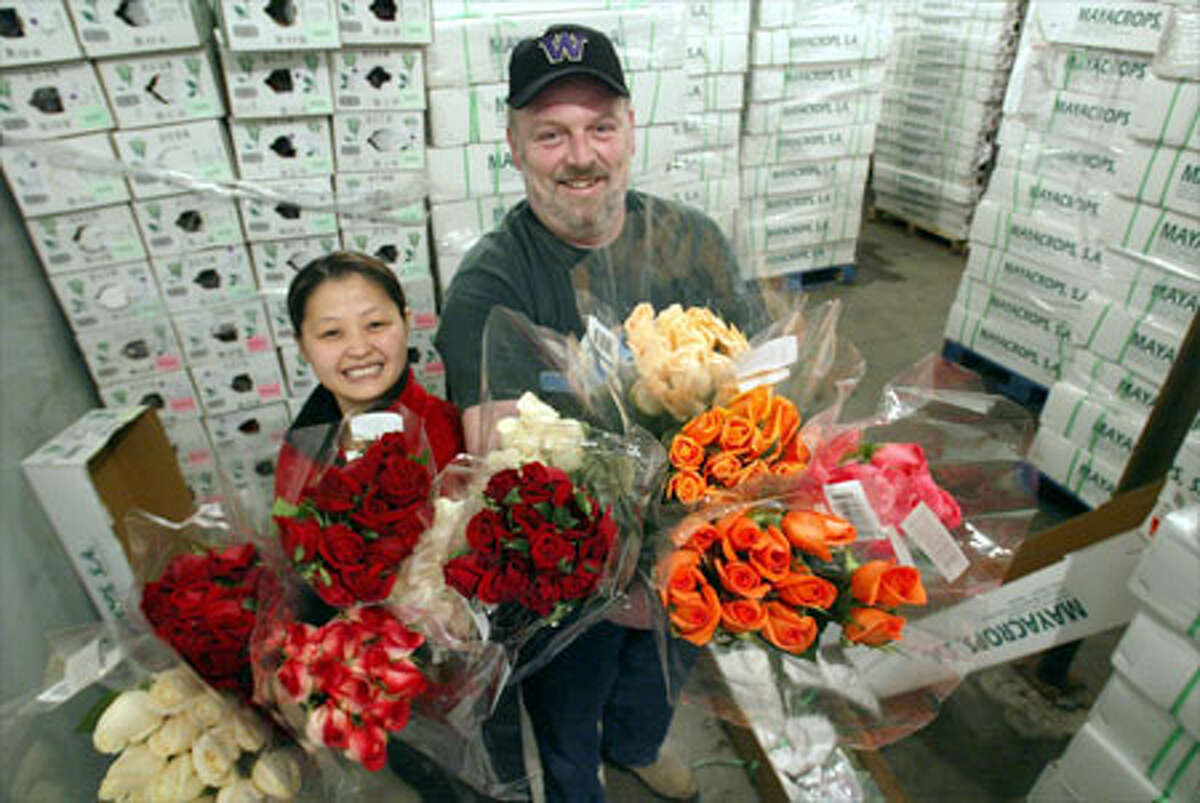 Express Northwest employees Eang Ear and Jeff Orr are surrounded by cases and cases of roses unwanted by the store that ordered them.