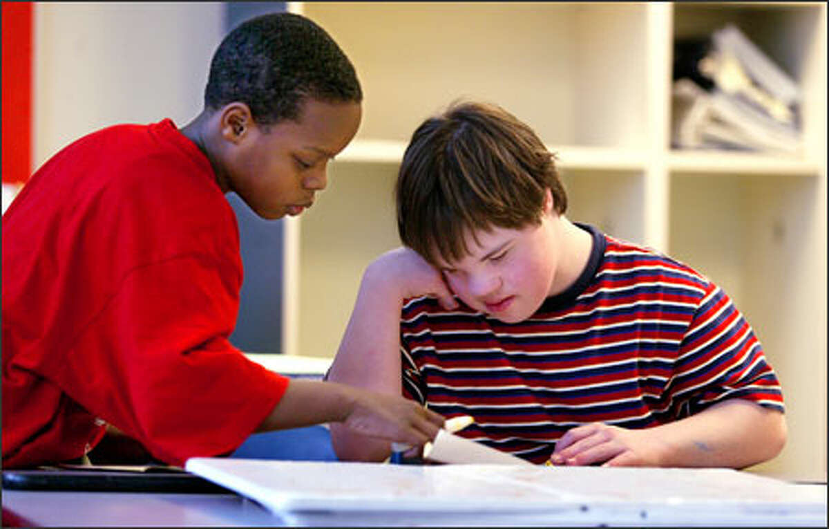 Timothy McMillon, 11, left, helps Andrew Scott, 13, with a project on Martin Luther King Jr. at TOPS K-8 in Seattle.