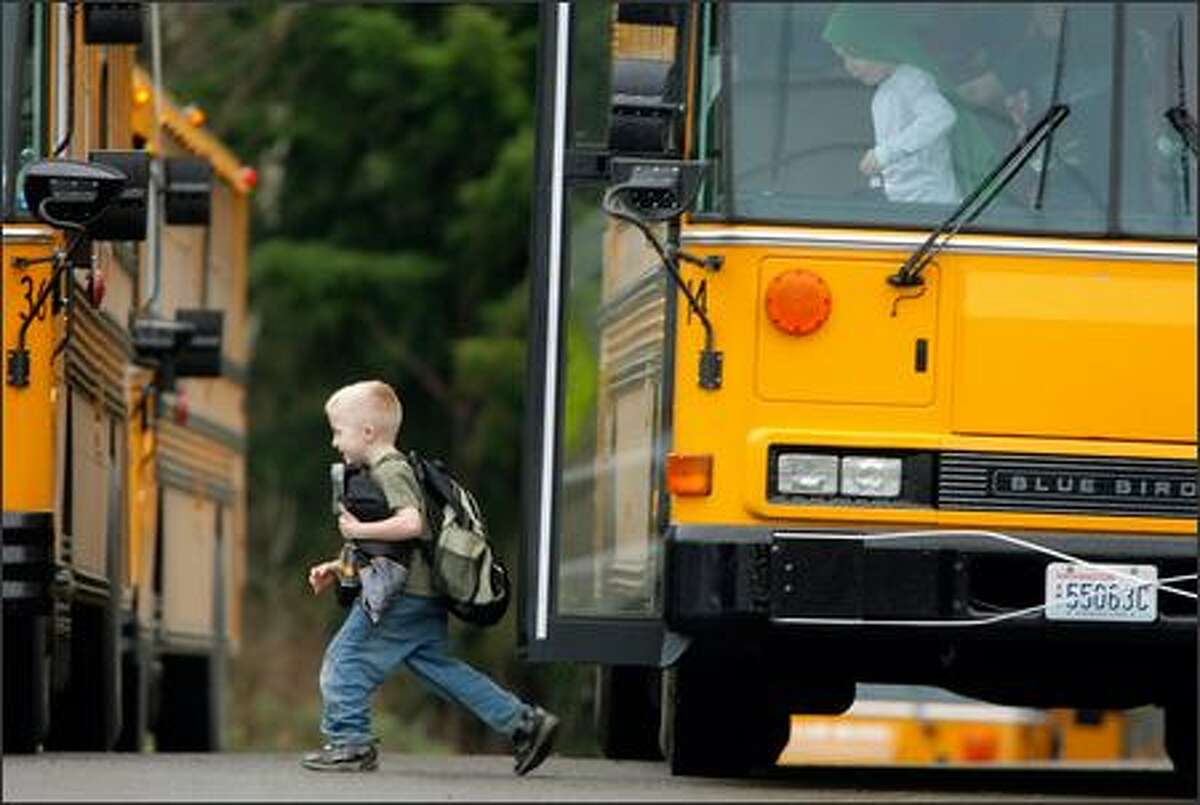 Students return to Westwood Elementary School in Enumclaw Tuesday after being evacuated earlier when damage from a homemade explosive device was discovered. The damage was confined to four windows and an air duct but as a precaution, the 345 elementary students were moved to a nearby school.