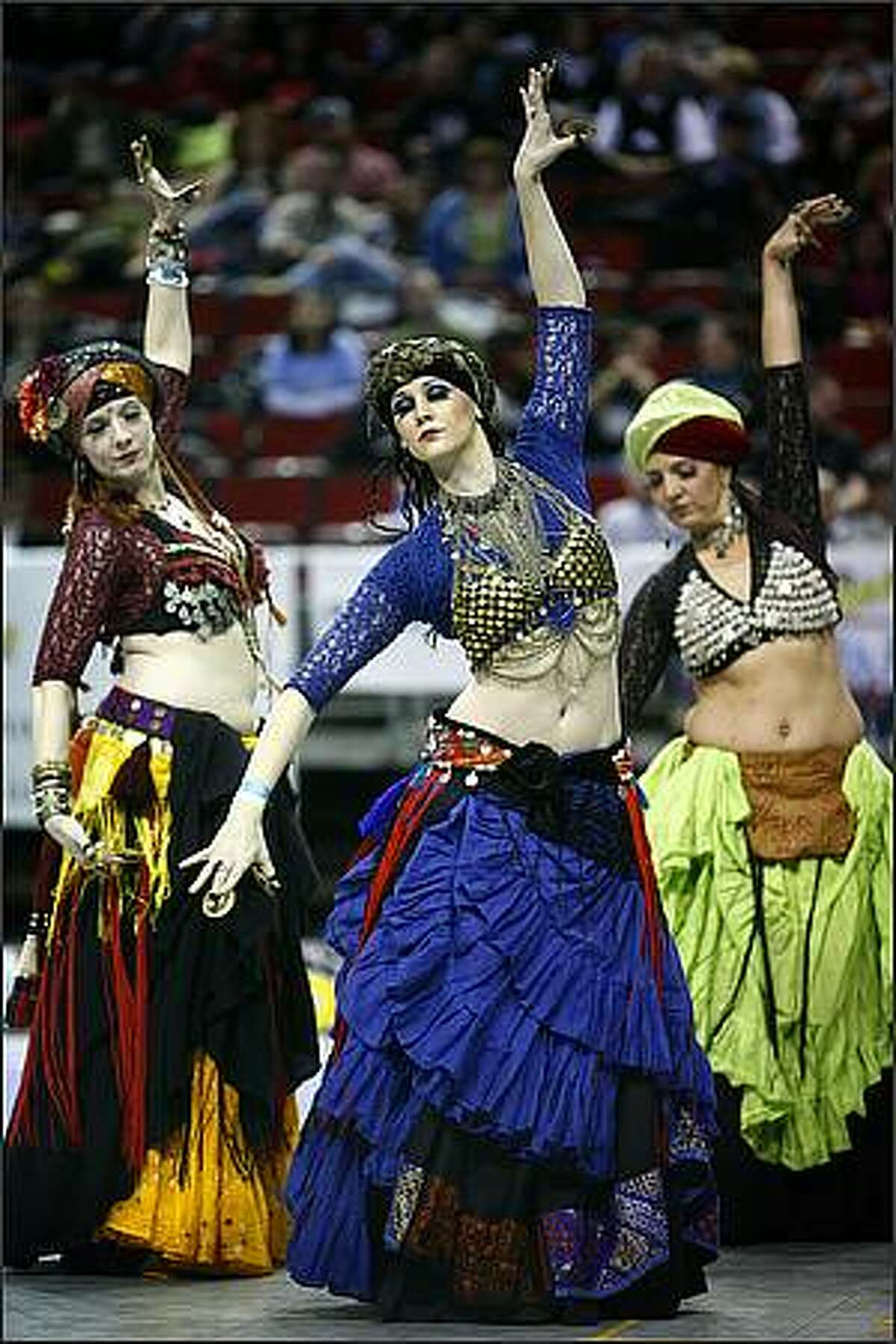 Susie Roman, a member of Skin Deep belly dancing troop, center, performs with other dancers during the Rat City Rollergirls season opening bout at Key Arena.