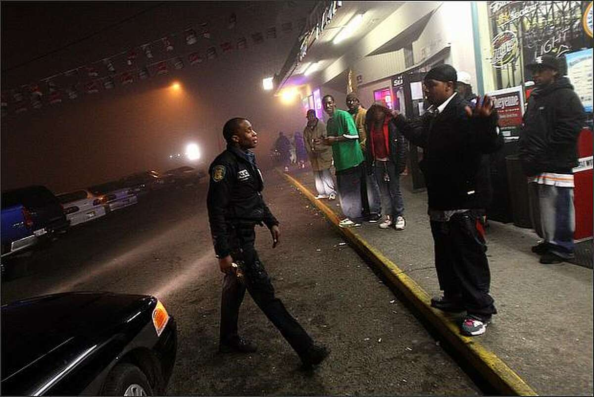 Seattle Police Officer Adley Shepherd approaches a young man in front of the bar Champs while on patrol in the south end of Seattle.