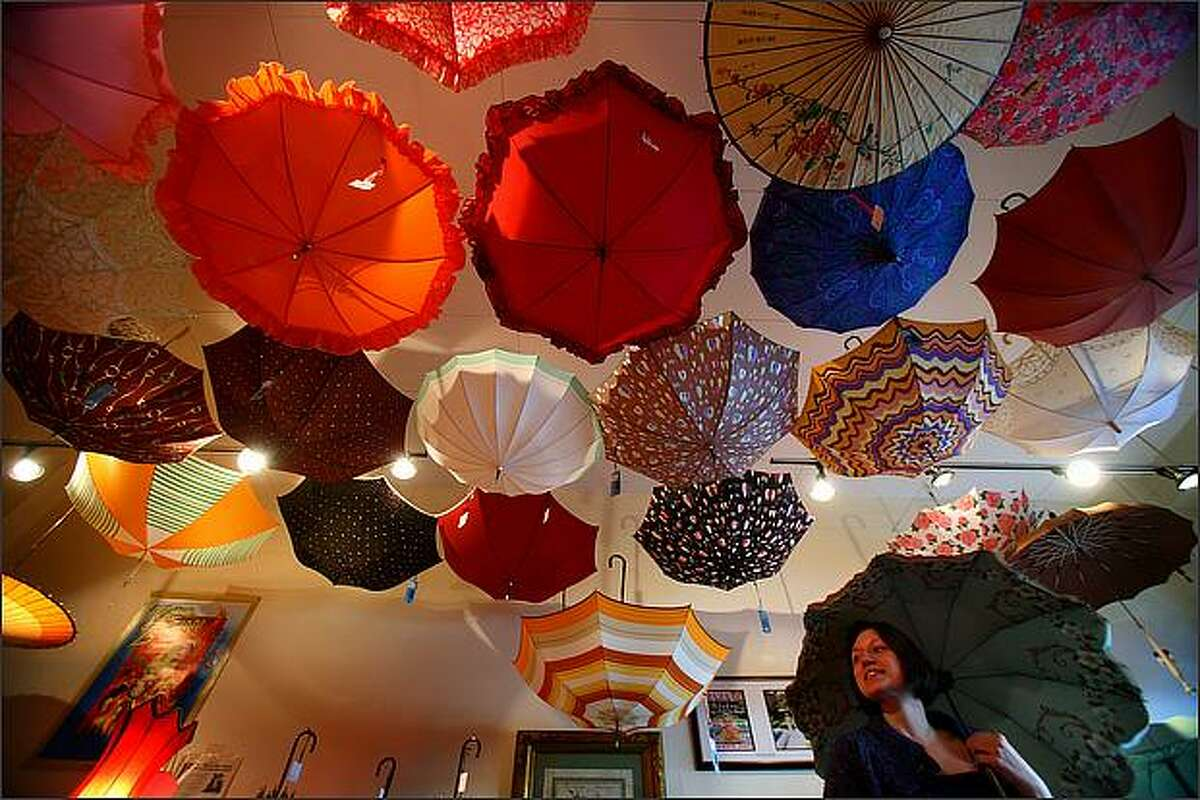 Customer Cheryl Wilson checks out one of the umbrellas at Bella Umbrella. The small shop rents and sells vintage and antique umbrellas.
