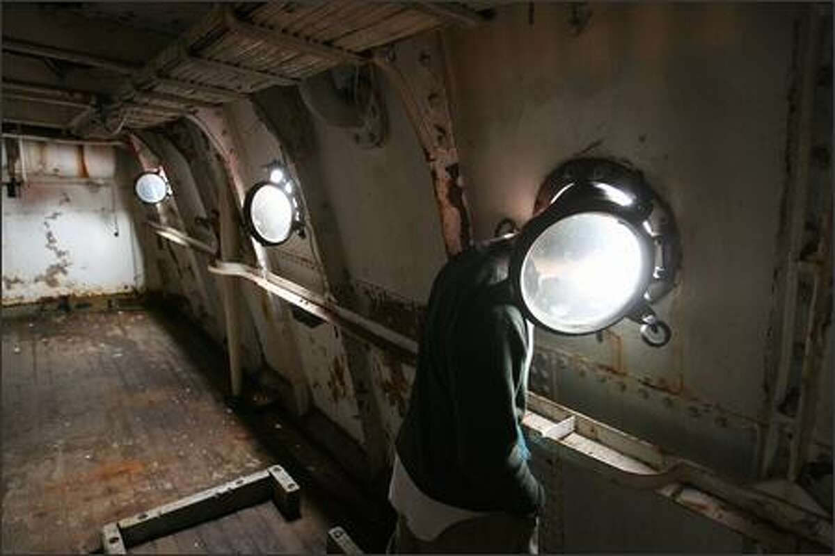 Edward Ehler, a senior at Ballard High School, pokes his head out of one of the portholes on the Swiftsure Lightship at the Historic Ships Pier on South Lake Union.
