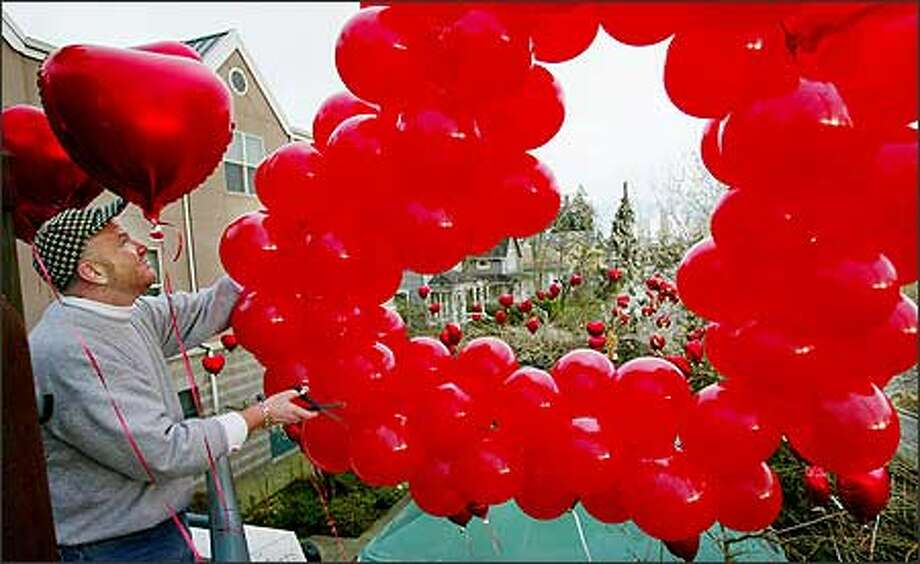 Matthew Behre and a team of volunteers and staff decorate the exterior and interior of Bailey-Boushay House with more than 800 helium-filled balloons in an annual celebration of Valentine's Day. Bailey-Boushay is a residential and day health care facility for people with HIV, AIDS and other illnesses. Photo: Paul Joseph Brown, Seattle Post-Intelligencer / Seattle Post-Intelligencer
