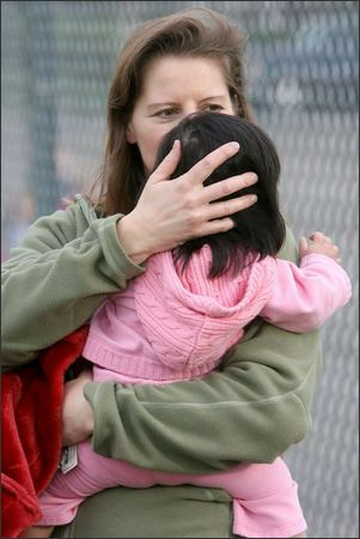 Janet Klimowich, whose daughter, Elisabeth, 6, is a kindergartener at Laurelhurst Elementary, kisses daughter Hope, 1, outside the school Thursday after hearing of the death of Marija Alumbaugh.