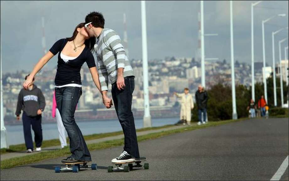 "Angie Sherbina, 16, and her boyfriend Rod Lats,19, both from Federal Way, Wash., skateboard along Alki Beach on Harbor Ave. and Alki Ave. SW on Valentine's Day. ""After this I'm going to surprise her with something,"" said Rod ""and then take her out to dinner."" The couple spent the ""whole day hanging out together"". ""Being together on a sunny day is just great."" said Rod. Photo: Karen Ducey, Seattle Post-Intelligencer / Seattle Post-Intelligencer"