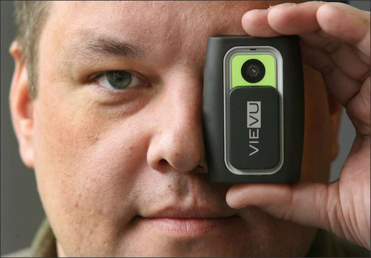 Former Seattle Police Officer Chris Myers displays a VieVu, a pager-sized camera for police officers to wear on their uniforms to record interactions during traffic stops and arrests, at the company's Seattle office. Three former Seattle police officers and a civilian administrative assistant from SPD make up the company.