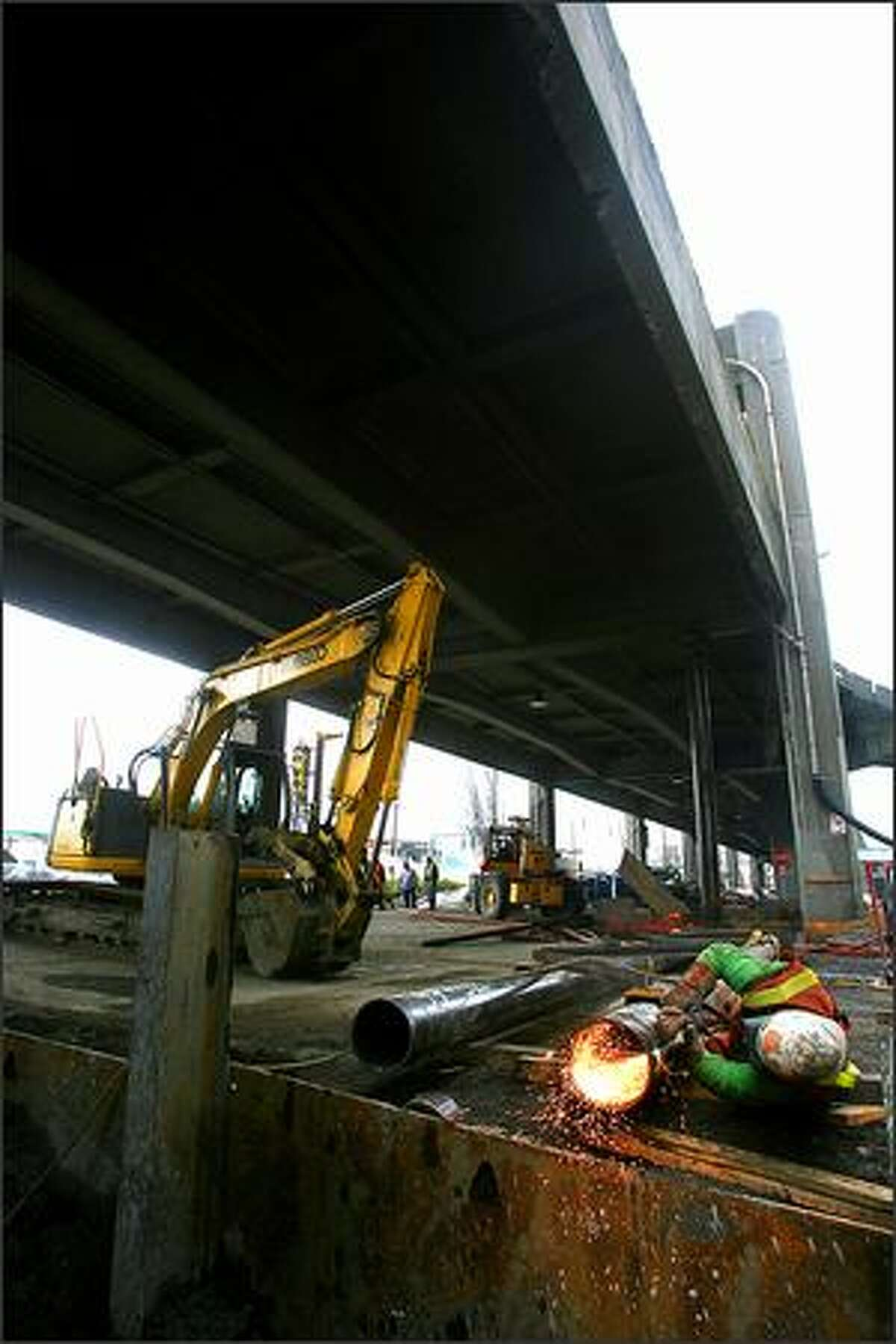 Doug Woods uses an oxy acetylene cutting torch as he cuts off the bottom of one of the temporary support columns that will be used to stabalize the viaduct during construction.