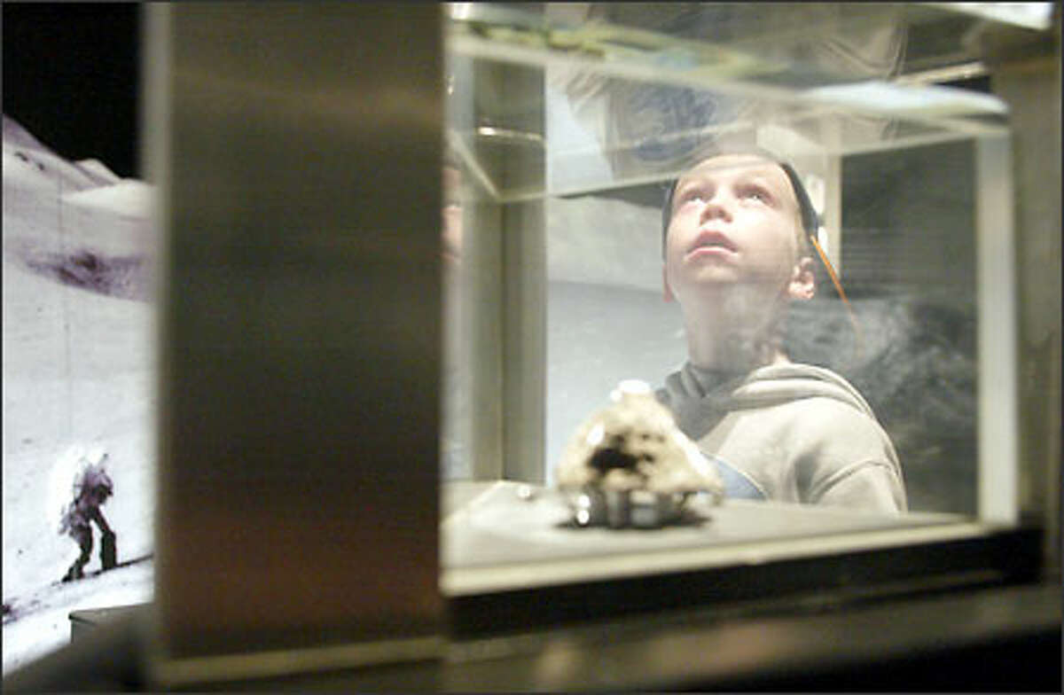 From the look on his face, Nathan Kearney may be dreaming of someday entering the space program, as the first-grader from Kirkland looks skyward while investigating a moon rock at the Pacific Science Center's