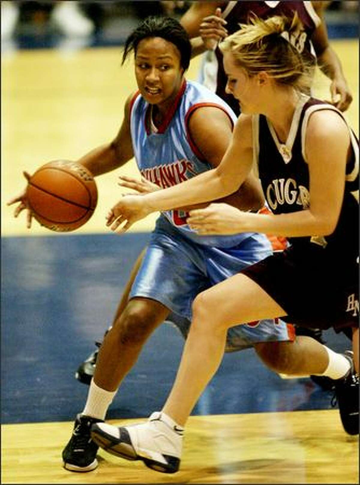 Chief Sealth's Christina Nzekwe drives past Holy Name's Devin Brooks. Nzekwe scored 15 ponts and Brooks scored 17.