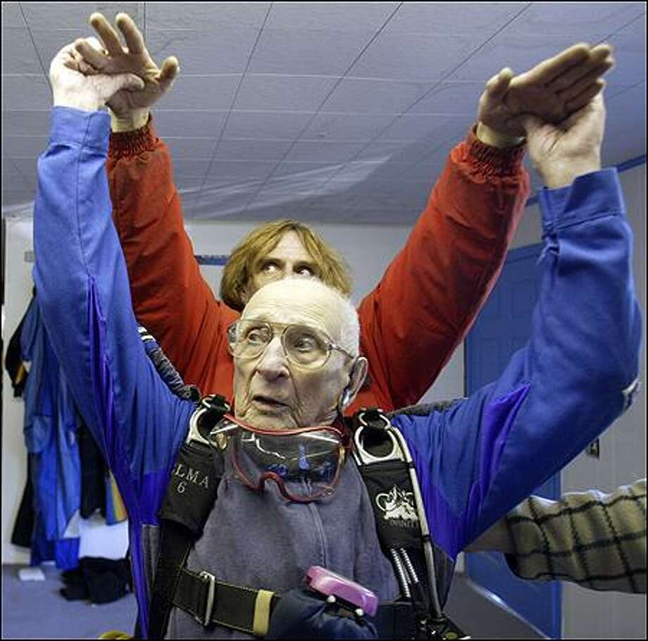 At 96, Milburn Hart made history Friday -- though not without a price -- when he jumped from a plane in Bremerton, making his way into the Guinness World Records as the oldest person to skydive solo. In  this photo, Hart practices reaching for his steering lines before his jump, which went well, except for the fact that he broke his arm when he missed his landing target, landing in brush. He said he expects to jump again -- after he heals. Photo: Jim Bryant, Seattle Post-Intelligencer / Seattle Post-Intelligencer