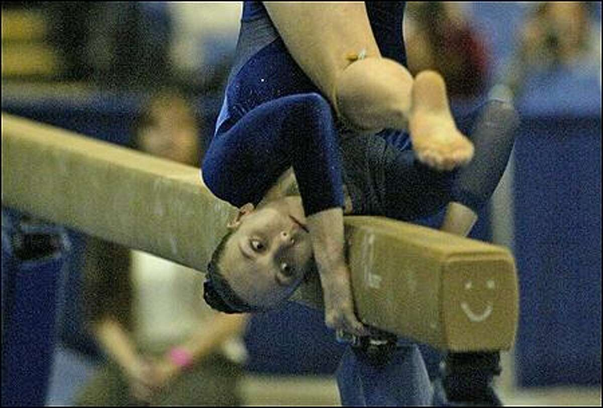 Liberty's Kara Bennett gets added support from a smiley face on the beam during the state championships.