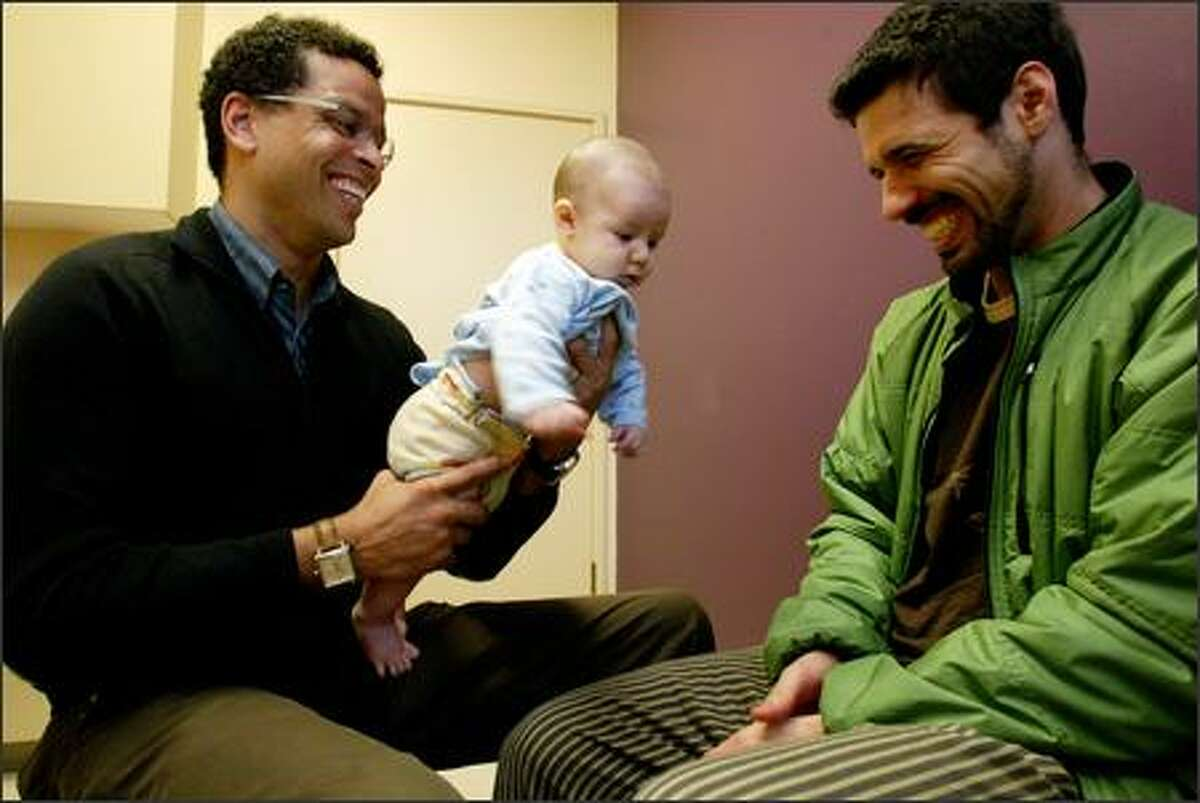 Dr. Ben Danielson, the medical director of Odessa Brown Children's Clinic since 1999, examines 12-week-old Kaveh Swartzman with his father, Aaron Swartzman.