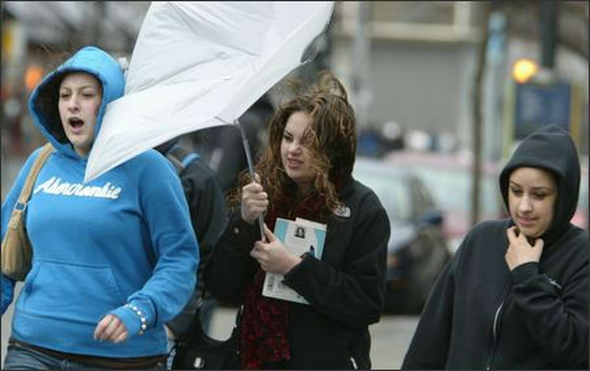 Michelle Reynolds, 19, center, tries to control her umbrella after getting hit by a gust of wind on Pine Street in downtown Seattle. Michelle and her friends Melissa Kleppinger, left, and Rachel Proefke, right, are students at the University of Washington.