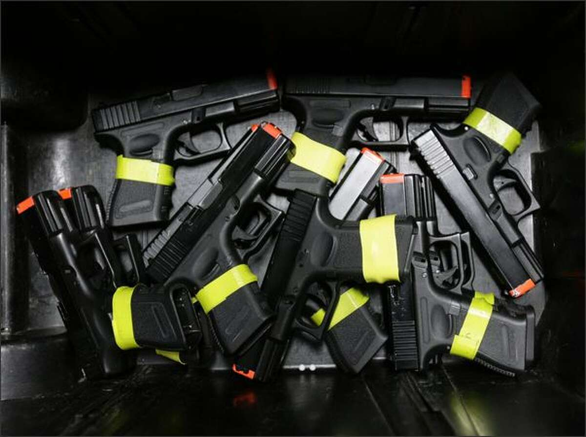 A bin full of Airsoft Gllock replicas, marked with yellow bands to show they aren't real guns, is available to officers at the SPD training facility in Seattle. The BB guns allow officers to repeatedly practice firing on-target in a realistic situation.