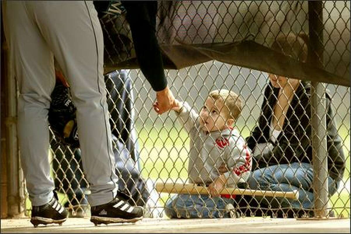 Thomas Brown, 2, of Peoria, shakes hands through the batting cage with Mariners pitcher Joel Pineiro.