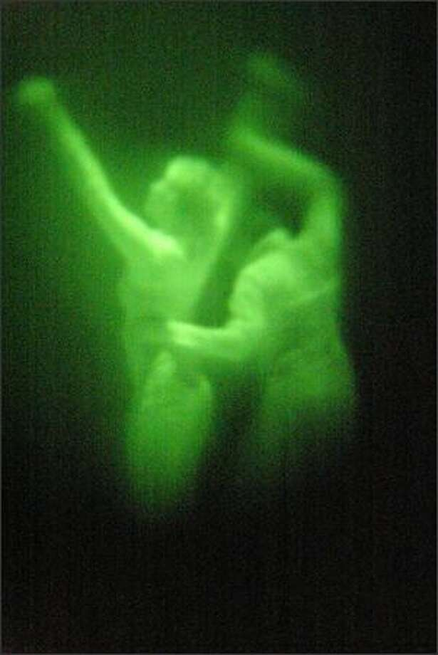 """Heather Budd and Jules Skloot rehearse """"Dark Room,"""" a performance art installation at the Western Bridge gallery in which dancers perform in the dark while the audience watches through night-vision goggles. Photo: Mike Urban, Seattle Post-Intelligencer / Seattle Post-Intelligencer"""