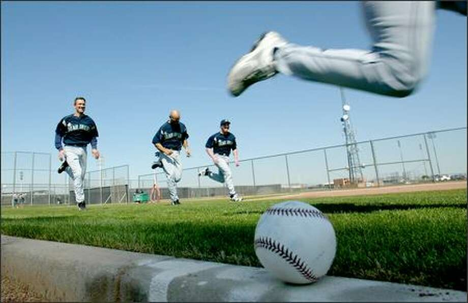 Randy Winn, whose right leg is the only part showing in this photo, sprints ahead of, from left, John Olerud, Raul Ibanez and Scott Spiezio during timed sprints. Photo: Mike Urban, Seattle Post-Intelligencer / Seattle Post-Intelligencer