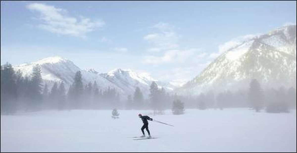 As the surrounding hills bask in the morning sun, Rob Fallon of Leavenworth skate skis through a soft fog blanketing the Icicle River Trail.