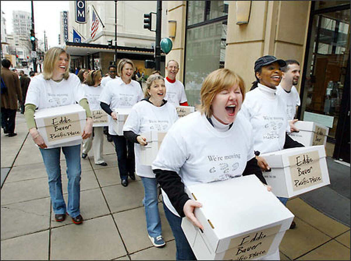 Deborah Anderson, front, leads more than 350 Eddie Bauer Inc. employees as they move merchandise and supplies Thursday from the company's downtown Seattle flagship store to its new location in Pacific Place. The new, 7,500-square-foot store will open Thursday. Brooks Brothers will begin construction next week in the old Eddie Bauer space for a new Northwest flagship store.