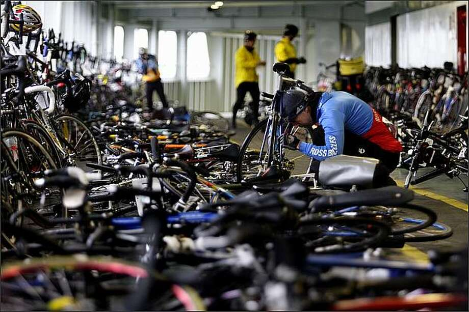 John Loomis of Enumclaw works on his bike while on the ferry to Bainbridge Island to take part in the Chilly Hilly bicycle ride. Photo: Andy Rogers, Seattle Post-Intelligencer / Seattle Post-Intelligencer