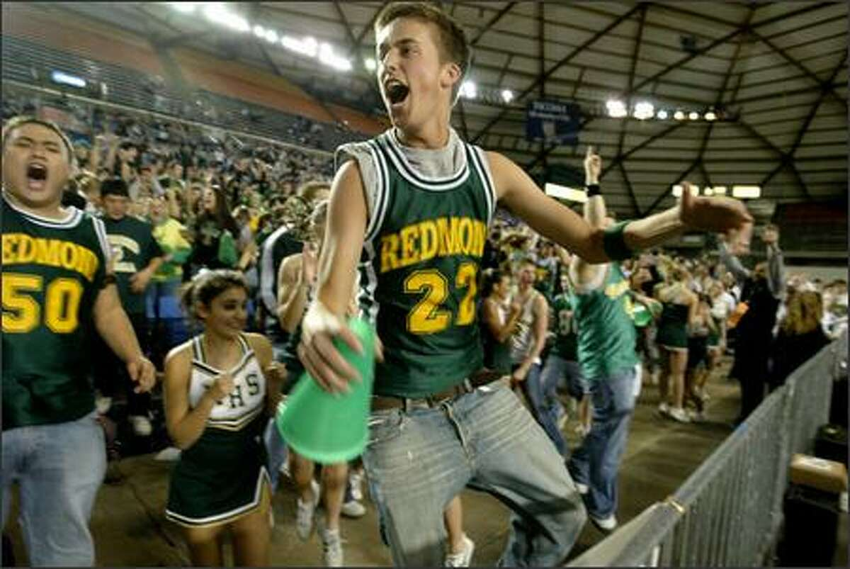 Redmond senior Spencer Burnstead gets airborne as he celebrates the Redmond High School upset of Federal Way High School 64-62 in the first round of the 4A boys' basketball state playoffs at the Tacoma Dome in Tacoma on Wednesday.