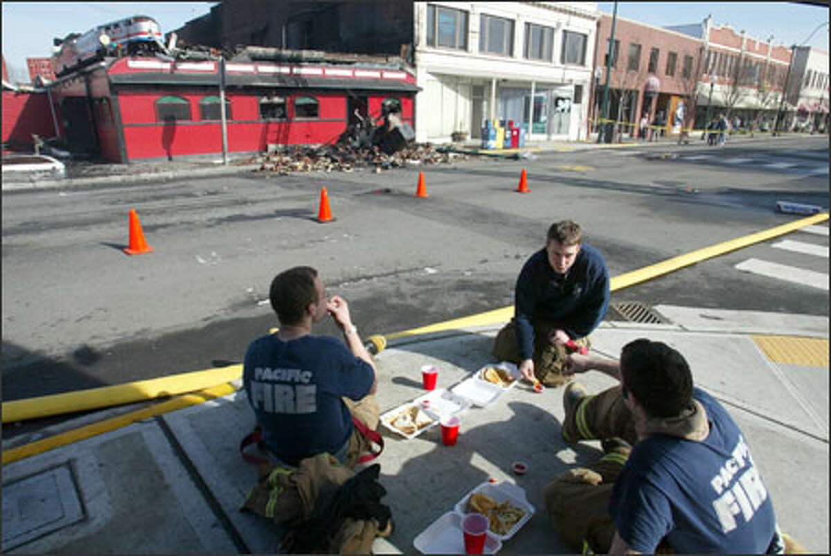 Kevin O'Keefe, left, Chris Archer and Kyle Koskovich of the Pacific Fire Department take a lunch break after fighting the blaze at KC's Caboose Cafe in Sumner.