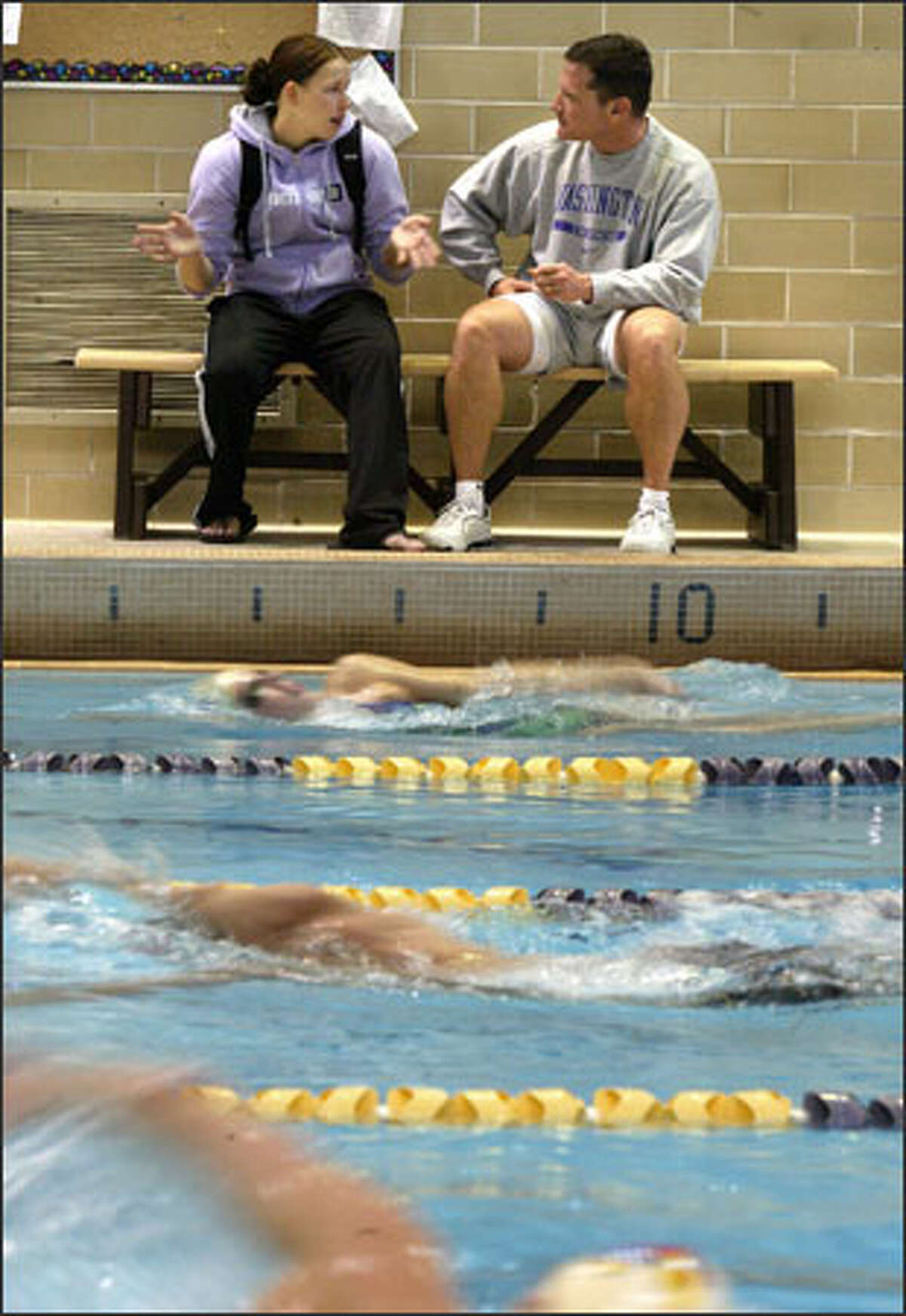 Mickey Wender, who coaches both the men's and women's swim teams at the University of Washington, talks with Caitlyn Shortt during a UW men's practice.