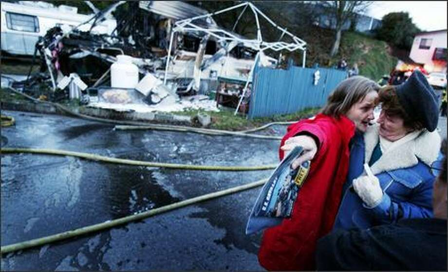 Regenia Hendrix offers her neighbor, Lori Schreiner, a place to stay after a fire started by a gas leak destroyed Schreiner's home near Northeast 88th Street and Lake City Way Northeast. Photo: Joshua Trujillo, Seattlepi.com / seattlepi.com