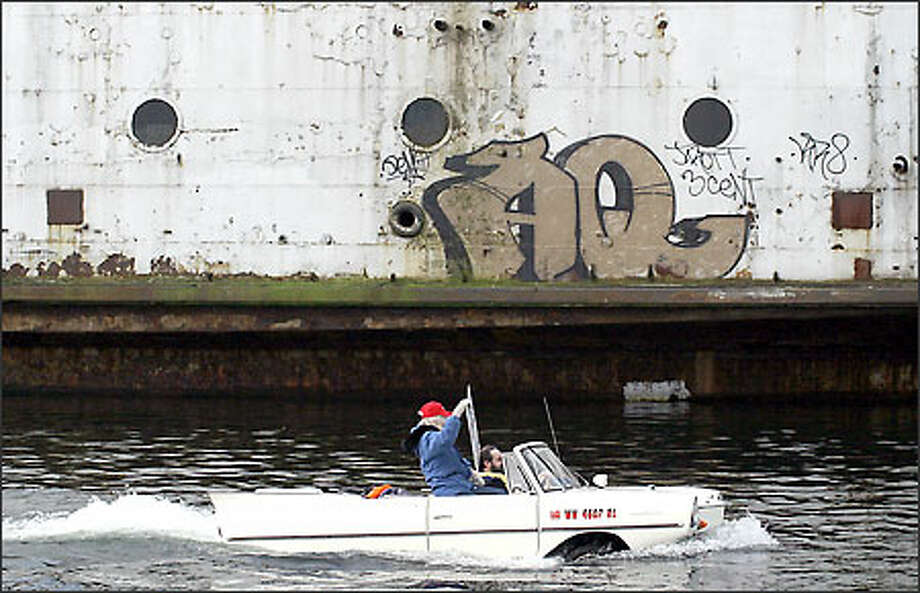 Roger St. John of Auburn drives his 1963 Amphicar with Cherie Kidd, president of the Kalakala Club in Port Angeles, in front of the Kalakala in Lake Union Tuesday. Photo: Rae Holtsbaum, Seattle Post-Intelligencer / Seattle Post-Intelligencer