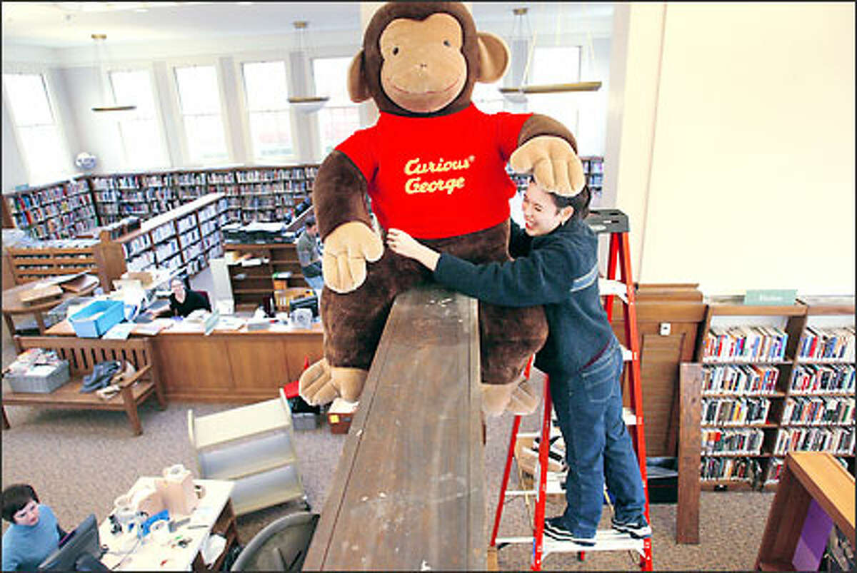 Jonis Black, librarian at the Green Lake Branch of the Seattle Public Library, secures the well-known children's literary figure Curious George in place in preparation for Saturday's reopening of the library. The reopening marks the sixth project completed under the Seattle Public Library's 1998 voter-approved building program.