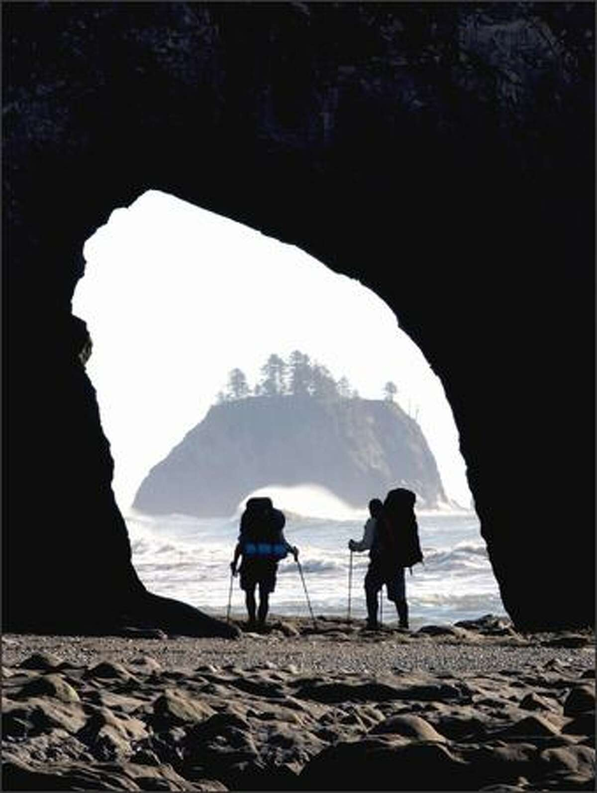 Hikers make their way at low tide through Hole in the Wall north of Rialto Beach on the Washington coast.