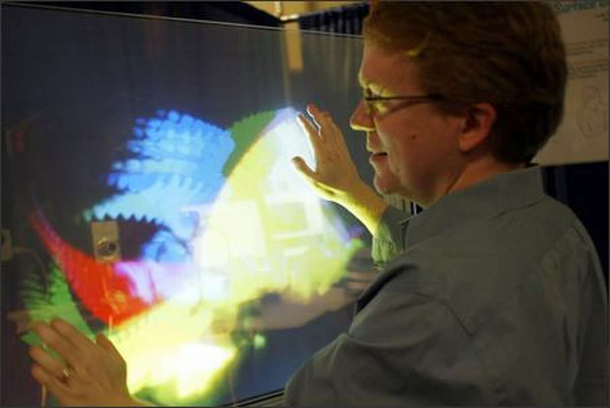 Microsoft researcher Andy Wilson uses his TouchLight project at the annual Microsoft Research TechFest at the campus in Redmond yesterday. His project is an example of efforts by researchers to use different surfaces as alternative computer interfaces. About 150 projects were on display.